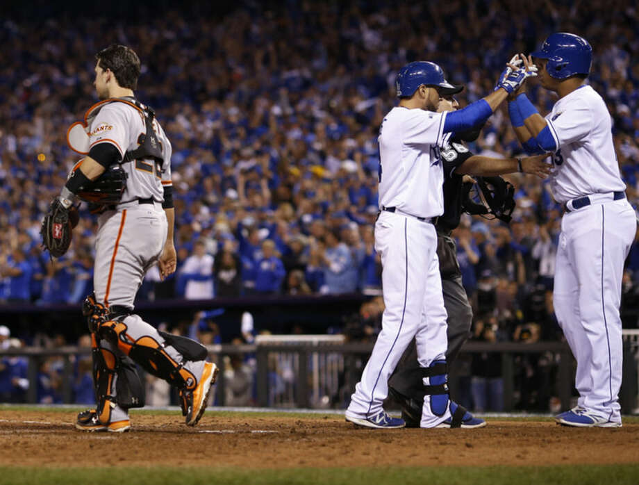 San Francisco Giants catcher Buster Posey walks past as Kansas City Royals Salvador Perez, right, congratulates teammate Omar Infante after Infante's two-run home run during the sixth inning of Game 2 of baseball's World Series Wednesday, Oct. 22, 2014, in Kansas City, Mo. (AP Photo/Matt Slocum)