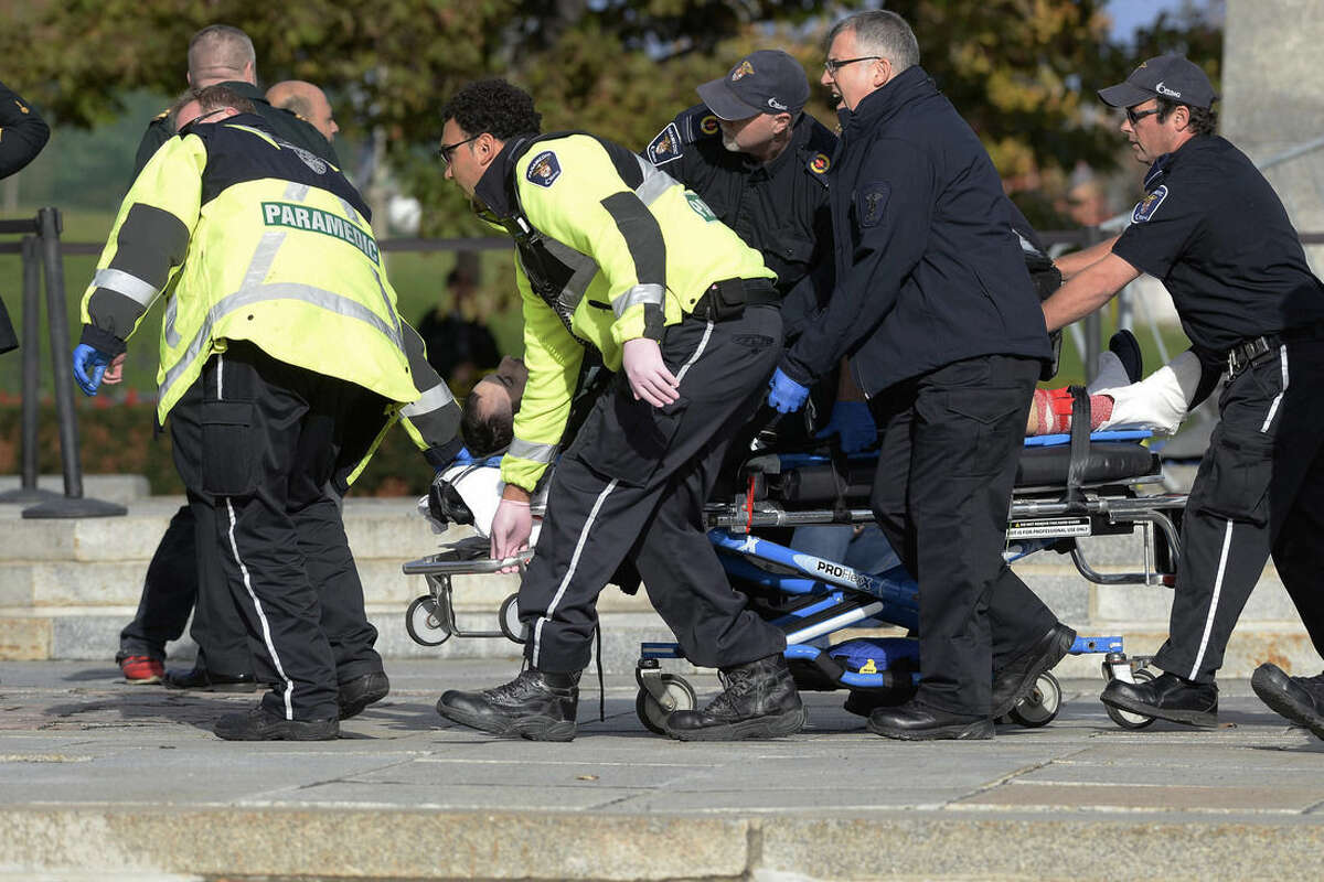 Paramedics and police pull a victim away from the Canadian War Memorial in Ottawa, Ontario, on Wednesday, Oct. 22, 2014. A soldier standing guard at the National War Memorial was shot by an unknown gunman and people reported hearing gunfire inside the halls of Parliament. Prime Minister Stephen Harper was rushed away from Parliament Hill to an undisclosed location, according to officials. (AP Photo/The Canadian Press, Adrian Wyld)