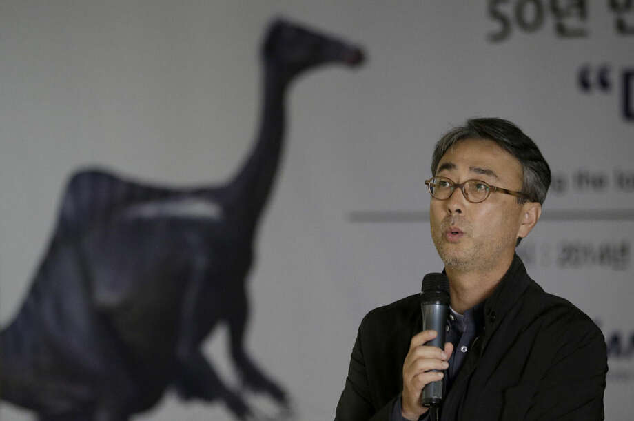 In this photo taken Wednesday, Oct. 22, 2014, study lead author Lee Yuong-nam, director of the Geological Museum, speaks to the media during a news conference in Seoul, South Korea, Wednesday, Oct. 22, 2014. Nearly 50 years ago, scientists found bones of two large, powerful dinosaur arms in Mongolia and figured they had discovered a fearsome critter with killer claws. Now scientists have found the rest of the dinosaur and have new descriptions for it: goofy and weird. The beast probably lumbered along on two legs like a cross between TV dinosaur Barney and Jar Jar Binks of Star Wars fame. It was 16 feet tall and 36 feet long, weighing seven tons, with a duckbill on its head and a hump-like sail on its back. Throw in those killer claws, tufts of feathers here and there, and no teeth - and try not to snicker. (AP Photo/Lee Jin-man)