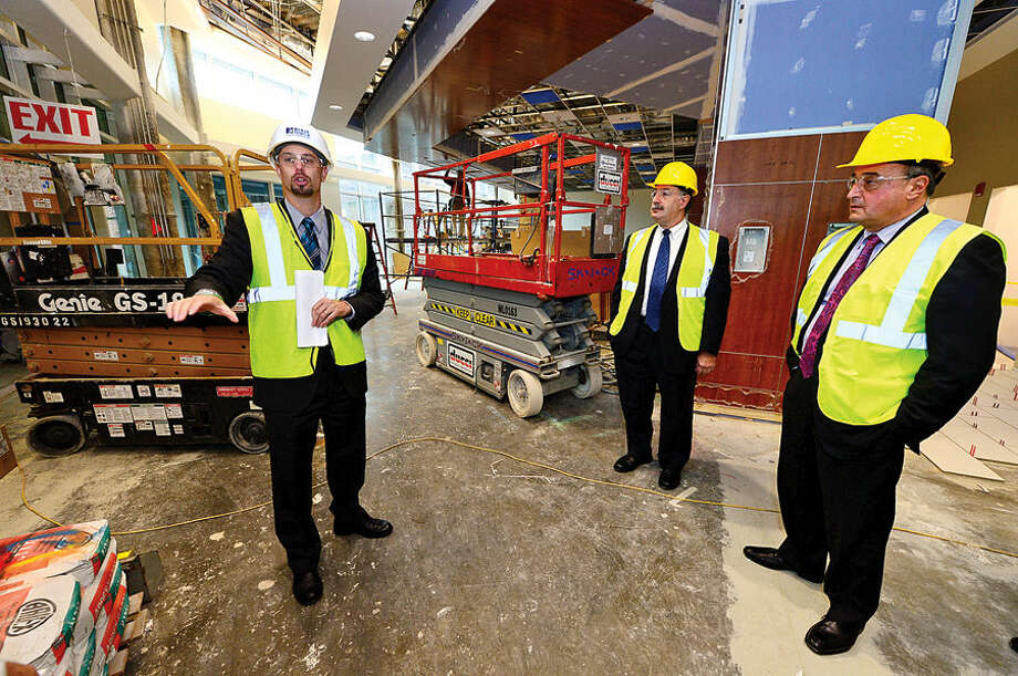 Hour photo / Erik Trautmann Norwalk Hospital Vice President of Operations, James Haynes, leads local officials on a tour of the lobby of the new Anne P. and Harold W. McGraw, Jr., Center, a five-story, 95,500-square-foot addition, slated for completion in 2015.