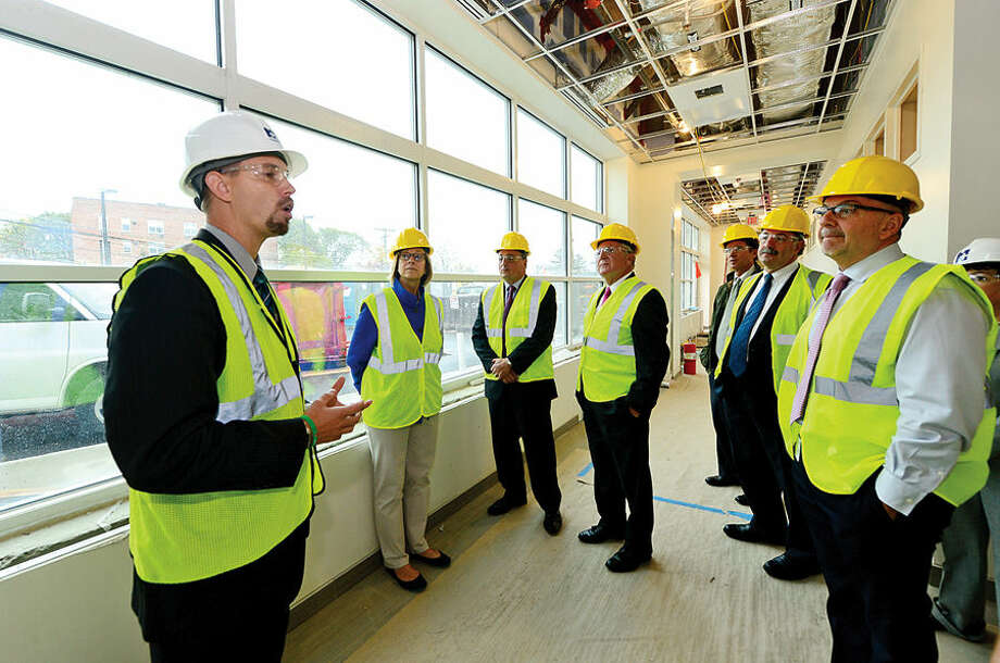 Hour photo / Erik Trautmann Norwalk Hospital Vice President of Operations, James Haynes, left, leads local officials on a tour of the new Anne P. and Harold W. McGraw, Jr., Center, a five-story, 95,500-square-foot addition, slated for completion in 2015.