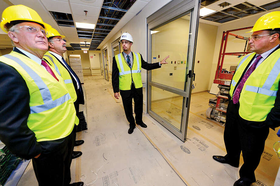 Hour photo / Erik Trautmann Norwalk Hospital Vice President of Operations, James Haynes, center, leads elected officials on a tour of the Emergency Department in the new Anne P. and Harold W. McGraw, Jr., Center, a five-story, 95,500-square-foot addition, slated for completion in 2015.