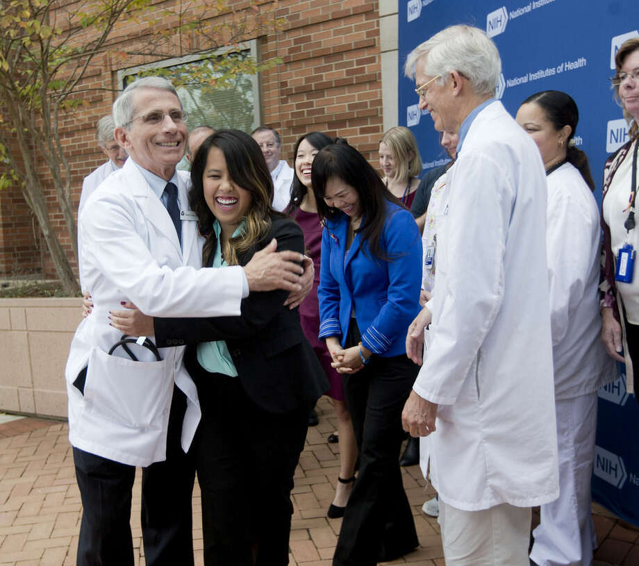 Patient Nina Pham is hugged by Dr. Anthony Fauci, director of the National Institute of Allergy and Infectious Diseases outside of National Institutes of Health (NIH) in Bethesda, Md., Friday, Oct. 24, 2014. Pham, the first nurse diagnosed with Ebola after treating an infected man at a Dallas hospital is free of the virus. The 26-year-old Pham arrived last week at the NIH Clinical Center. She had been flown there from Texas Health Presbyterian Hospital Dallas. (AP Photo/Pablo Martinez Monsivais)