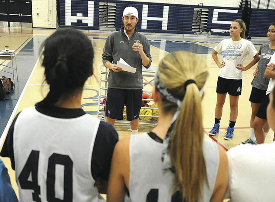 Photo by Matthew VinciFirst-year Wilton head coach Rob Coloney, center, speaks to his team during the first week of practice.