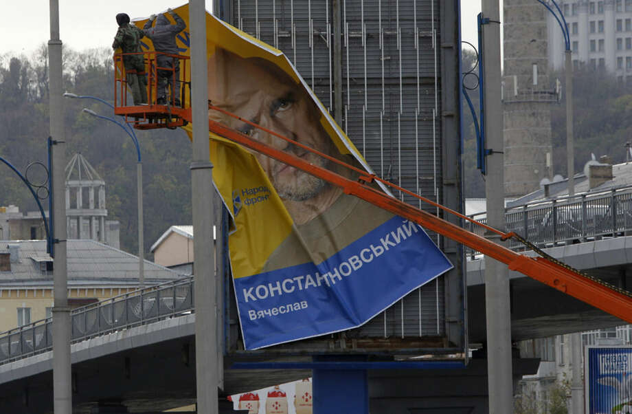 Street workers remove a pre-election poster in Kiev, Ukraine, Friday, Oct. 24, 2014, on the last official day of political campaigning, ahead of the parliamentary election on Sunday. (AP Photo/Sergei Chuzavkov)