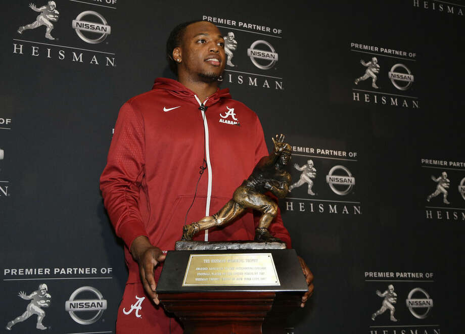 Alabama's Derrick Henry poses for photos with the Heisman Trophy, Friday, Dec. 11, 2015, in New York. Henry, along with Clemson's Deshaun Watson and Stanford's Christian McCaffrey, is a finalist for the trophy which recognizes college football's best player of the year. (AP Photo/Julie Jacobson)