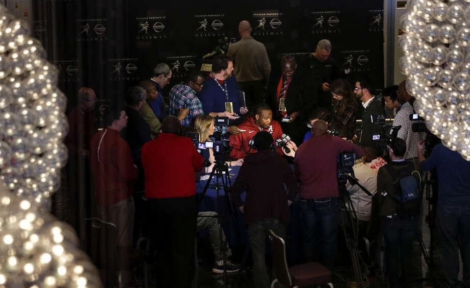 Alabama's Derrick Henry, center, answers questions for members of the media, Friday, Dec. 11, 2015, in New York. Henry, along with Clemson's Deshaun Watson and Stanford's Christian McCaffrey, is a finalist for the Heisman Trophy which recognizes college football's best player of the year. (AP Photo/Julie Jacobson)