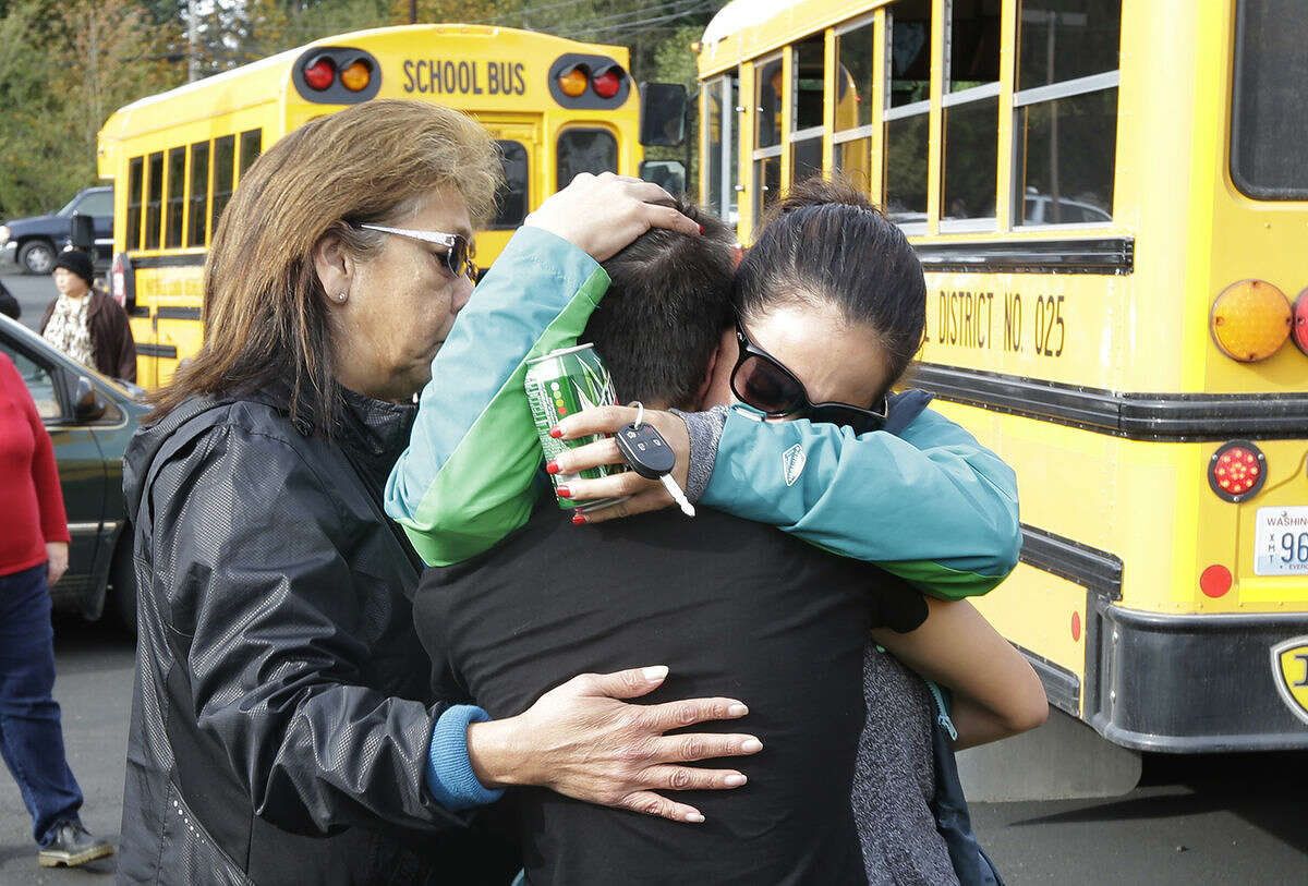 People embrace in front of school busses at a church Friday, Oct. 24, 2014, where students were taken to be reunited with parents following a shooting at Marysville Pilchuck High School in Marysville, Wash. (AP Photo/Ted S. Warren)