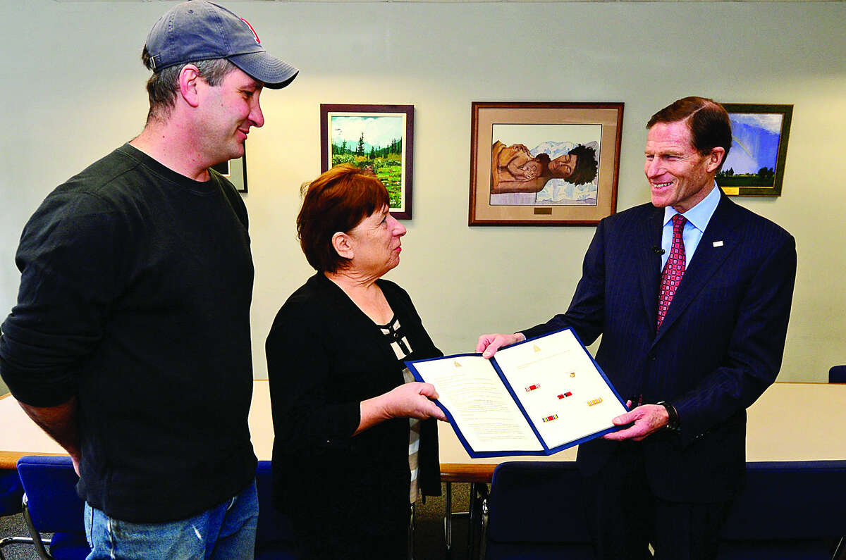 Hour photo / Erik Trautmann World War II veteran John Borriello is posthumously awarded service medals by US Senator Richard Blumenthal and presented to his daughter Linda Tanner and grandson, John Tanner, at Norwalk City Hall on Friday.