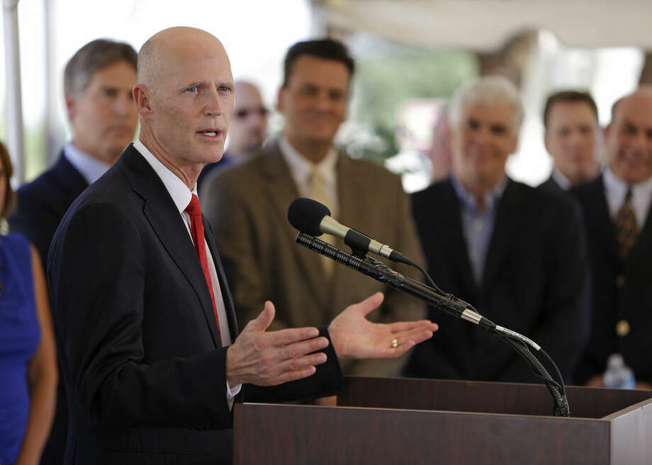 FILE- In this Oct. 17, 2013 file photo, Florida Gov. Rick Scott, left, announces to Photon-X employees and Osceola County officials that the company, Photon-X, will relocate to Osceola County, in Kissimmee, Fla. The move from Alabama is bringing more than 100 high-paying technical jobs to Florida. Elected four years ago, Scott, the businessman-turned-politician cut taxes, slashed regulations and recruited businesses to help revive the state's flagging economy. Now Florida is bouncing back, adding more than 638,000 jobs and cutting unemployment to 6.3 percent. (AP Photo/John Raoux, File)
