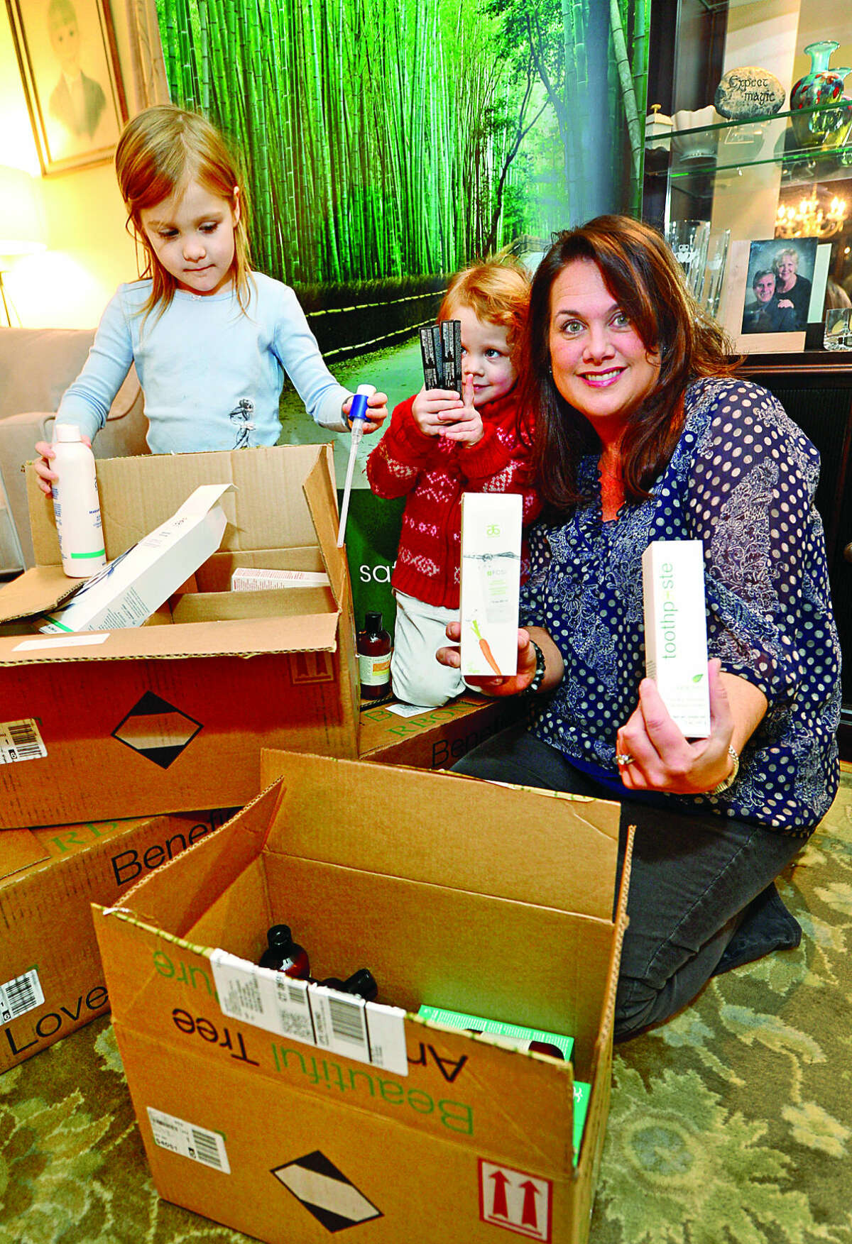 Hour photo / Erik Trautmann Weston resident Kristin Kreuder, an Arbonne Independent Consultant, and her daughters, Katherine, 4, and Victoria, 3, pack up boxes of Arbonne beauty and skincare products to be donated to Malta House in Norwalk for Christmas.