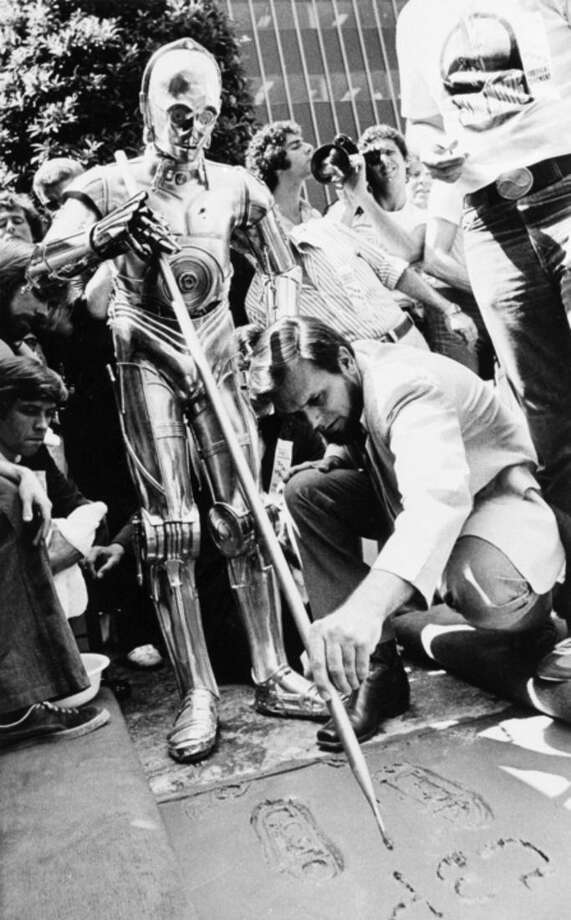 "FILE - In this Aug. 3, 1977 file photo, joining movie stars of the past and present, C-3PO, one of the famous robots from the 20th Century-Fox film ""Star Wars,"" places his foot prints in the cement in front of Mann's Chinese Theater in Los Angeles. Assisted by studio personnel, C-3PO signs his name and thereby joins such stars as Greta Garbo, Clark Gable and Barbra Streisand. The new film, ""Star Wars: The Force Awakens"" opens in U.S. theaters on Dec. 18, 2015. (AP Photo/Nick Ut, File)"