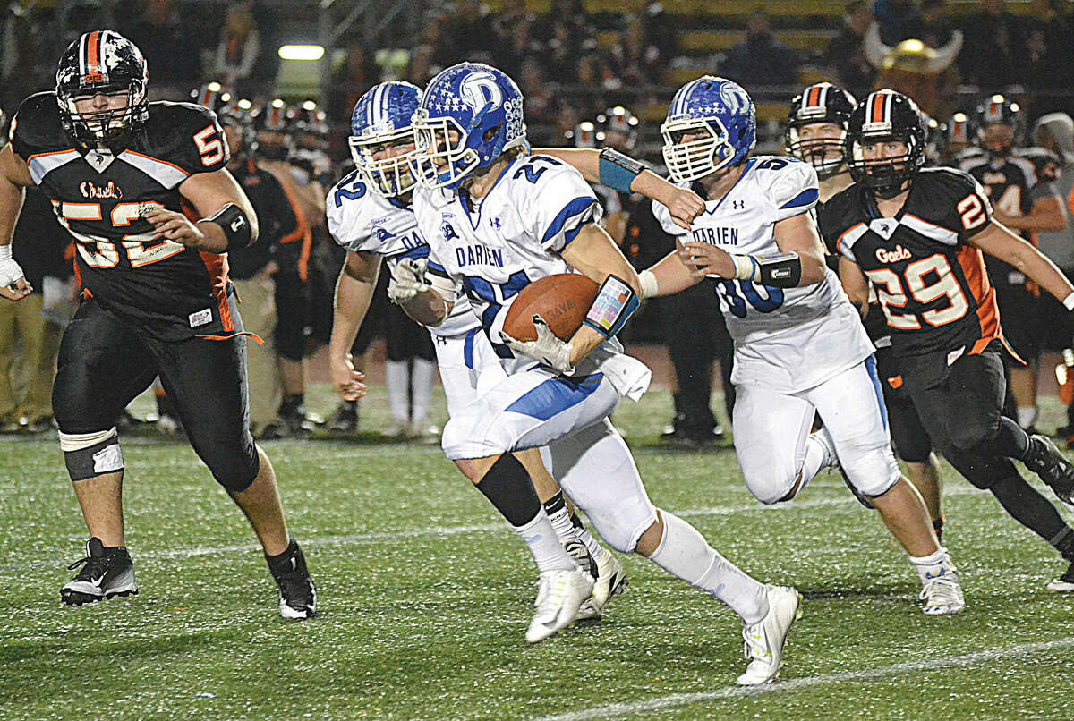 Hour photo/Pete Paguaga - Darien's Shelby Grant runs for a big gain against Shelton on Saturday during the second half of the Class LL state title game.