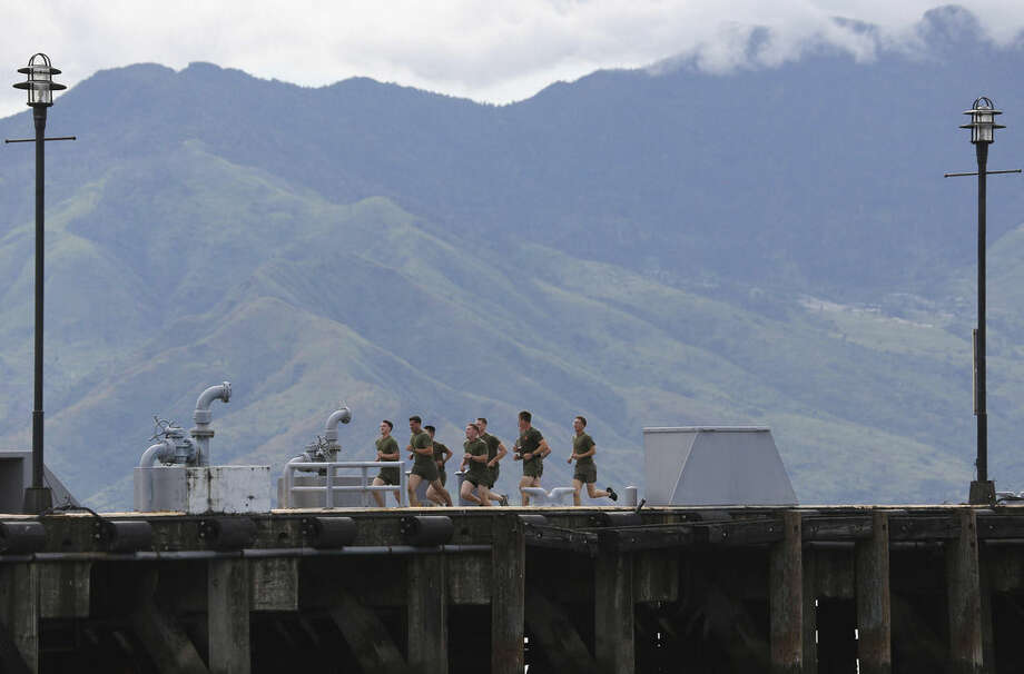 In this Saturday, Oct. 18, 2014 photo, U.S. Marines from the USS Peleliu, where U.S. Marine Pfc. Joseph Scott Pemberton is said to be detained after allegedly killing Filipino transgender Jennifer Laude, jog around the pier at the Subic Bay free port, Zambales province, northern Philippines. The killing of Laude, a 26-year-old transgender whose former name was Jeffrey, has sparked public anger in the Philippines and revived a debate over the U.S. military presence in a country seen by Washington as a major ally in Southeast Asia. The nations signed a new accord in April that allows greater U.S. military access to Philippine military camps, part of Washington's pivot back to Asia where it wants to counter rising Chinese might. (AP Photo/Aaron Favila)