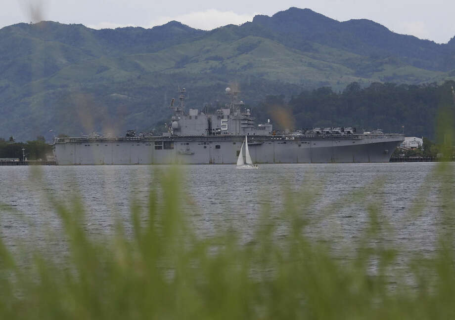 In this Friday, Oct. 17, 2014 photo, a yacht passes by the USS Peleliu, where U.S. Marine Pfc. Joseph Scott Pemberton is said to be detained after allegedly killing Filipino transgender Jennifer Laude, at the Subic Bay free port, Zambales province, northern Philippines. The killing of Laude, a 26-year-old transgender whose former name was Jeffrey, has sparked public anger in the Philippines and revived a debate over the U.S. military presence in a country seen by Washington as a major ally in Southeast Asia. The nations signed a new accord in April that allows greater U.S. military access to Philippine military camps, part of Washington's pivot back to Asia where it wants to counter rising Chinese might. (AP Photo/Aaron Favila)