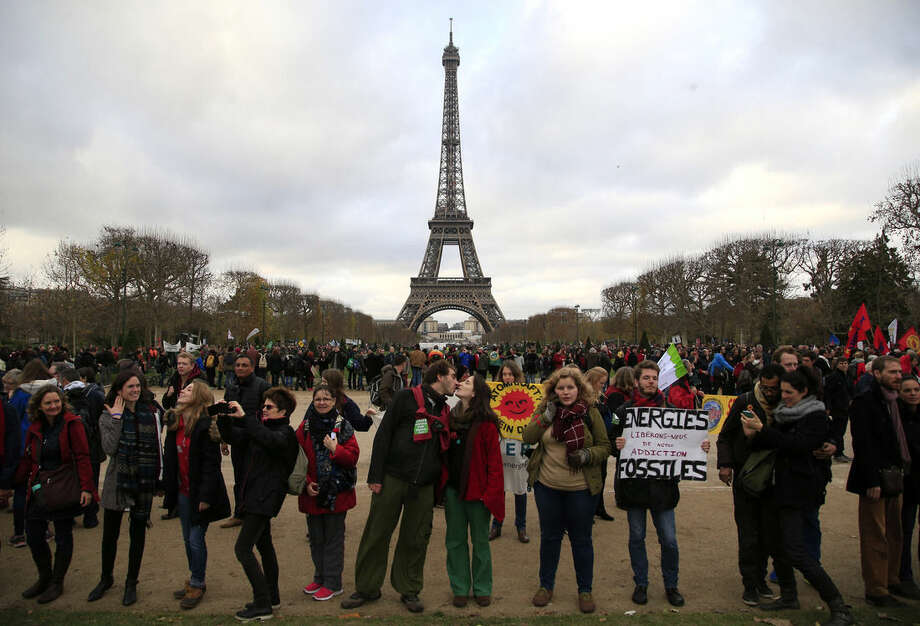 A couple kiss as activists demonstrate near the Eiffel Tower, in Paris, Saturday, Dec.12, 2015 during the COP21, the United Nations Climate Change Conference. As organizers of the Paris climate talks presented what they hope is a final draft of the accord, protesters from environmental and human rights groups gather to call attention to populations threatened by rising seas and increasing droughts and floods. (AP Photo/Thibault Camus)