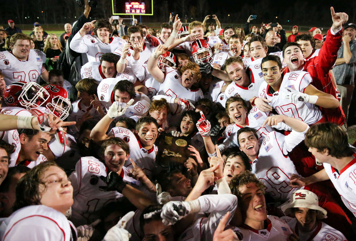 Hour photo/Chris Palermo New Canaan players pile on top of each other celebrating their victory over North Haven Saturday.