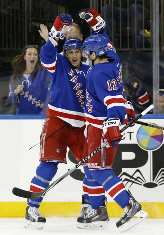 A fan reacts as New York Rangers right wing Lee Stempniak (12) congratulates left wing Carl Hagelin (62), of Sweden, after Hagelin scored a goal during the second period of an NHL hockey game against the San Jose Sharks at Madison Square Garden in New York, Sunday, Oct. 19, 2014. (AP Photo/Kathy Willens)