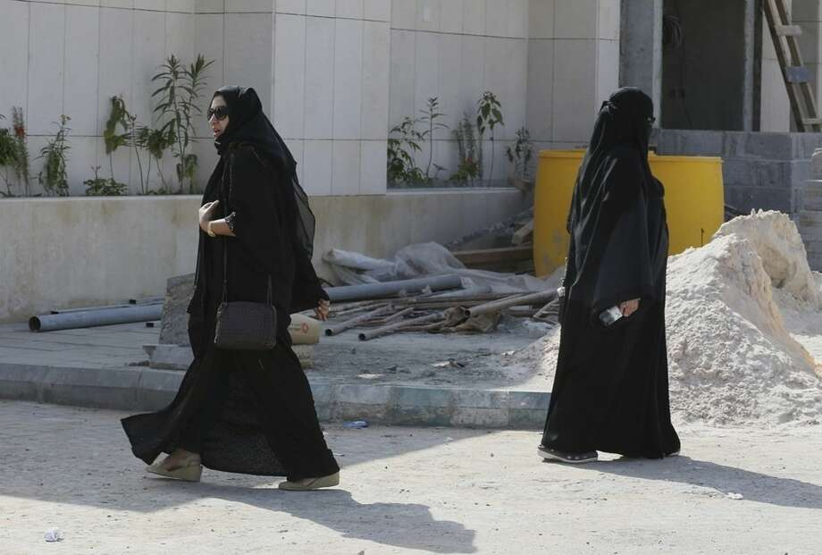 A Saudi woman, right, leaves the polling center after casting her vote as another woman prepares to enter during the country's municipal elections in Riyadh, Saudi Arabia, Saturday, Dec. 12, 2015. Women across Saudi Arabia marked a historic milestone on Saturday, both voting and running as candidates in government elections for the first time, but just outside polling stations they waited for male drivers — a reminder of the limitations still firmly in place. (AP Photo/Khalid Mohammed)