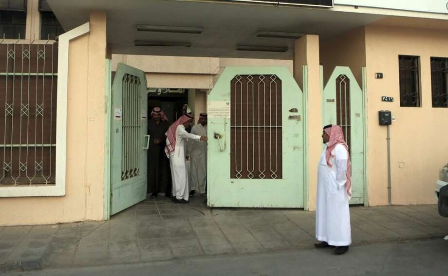 Saudi election officials close the gate at a polling center at the end for the country's municipal elections in Riyadh, Saudi Arabia, Saturday, Dec. 12, 2015. Women across Saudi Arabia marked a historic milestone on Saturday, both voting and running as candidates in government elections for the first time, but just outside polling stations they waited for male drivers — a reminder of the limitations still firmly in place. (AP Photo/Khalid Mohammed)