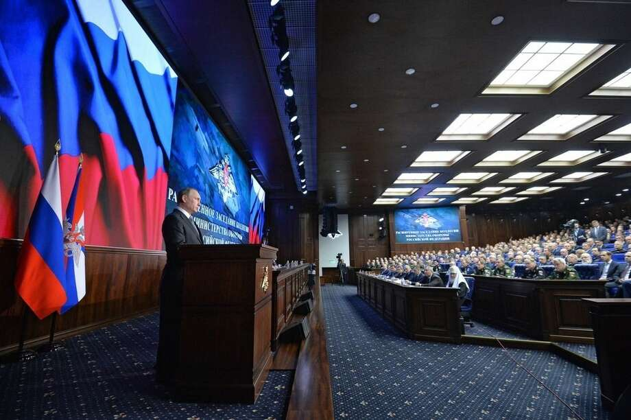 Russian President Vladimir Putin, left, delivers his speech during a meeting with top military officials in Moscow, Russia, Friday, Dec. 11, 2015. Putin said the Russian military action helped change the situation in Syria, supporting the Syrian army offensive. (Alexei Druzhinin, Sputnik, Kremlin Pool Photo via AP)