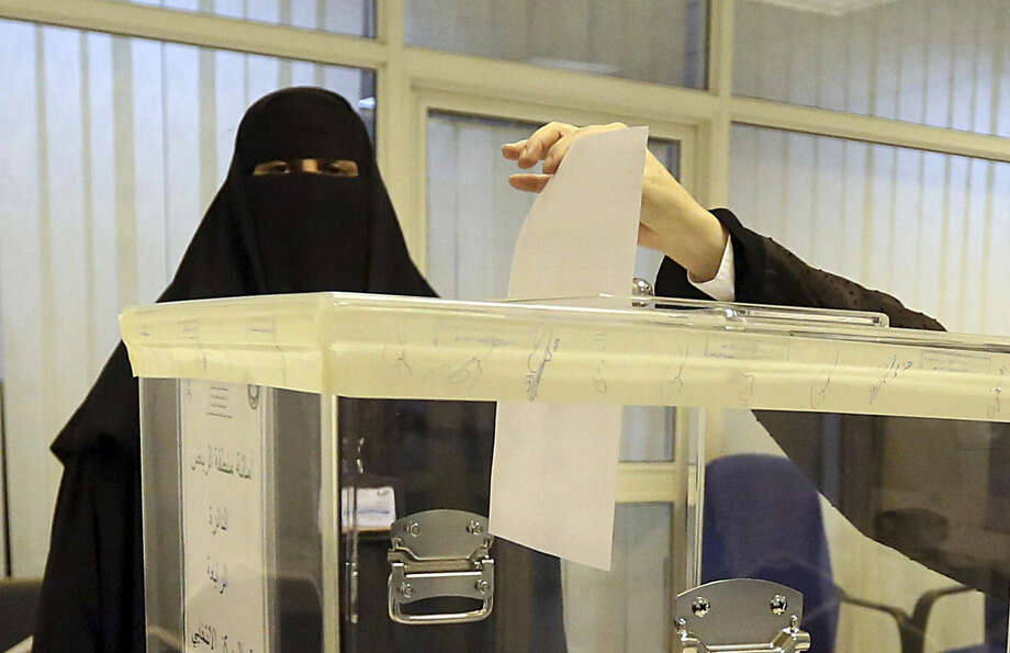 Saudi women vote at a polling center during the municipal elections, in Riyadh, Saudi Arabia, Saturday, Dec. 12, 2015. Women across Saudi Arabia marked a historic milestone on Saturday, both voting and running as candidates in government elections for the first time, but just outside polling stations they waited for male drivers — a reminder of the limitations still firmly in place. (AP Photo/Aya Batrawy)