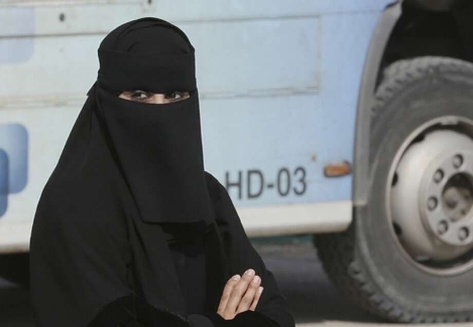A Saudi woman waits outside a polling center as she prepares to cast her ballot during the country's municipal elections in Riyadh, Saudi Arabia, Saturday, Dec. 12, 2015. Women across Saudi Arabia marked a historic milestone on Saturday, both voting and running as candidates in government elections for the first time, but just outside polling stations they waited for male drivers — a reminder of the limitations still firmly in place. (AP Photo/Khalid Mohammed)