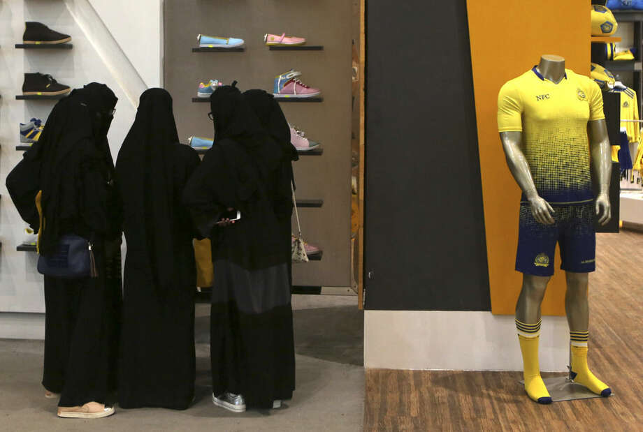 In this Friday, Dec. 11, 2015 photo, Saudi women shop at a mall in Riyadh, Saudi Arabia. Women across Saudi Arabia marked a historic milestone on Saturday, Dec. 12, 2015, both voting and running as candidates in government elections for the first time. (AP Photo/Khalid Mohammed)