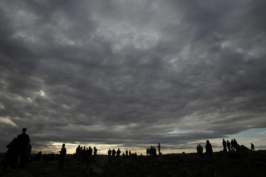 People gather on a hilltop on the outskirts of Suruc, at the Turkey-Syria border, to watch in the distance the fighting between Syrian Kurds and the militants of Islamic State group in Kobani, Syria, Sunday, Oct. 19, 2014. Kobani, also known as Ayn Arab, and its surrounding areas, has been under assault by extremists of the Islamic State group since mid-September and is being defended by Kurdish fighters. (AP Photo/Lefteris Pitarakis)