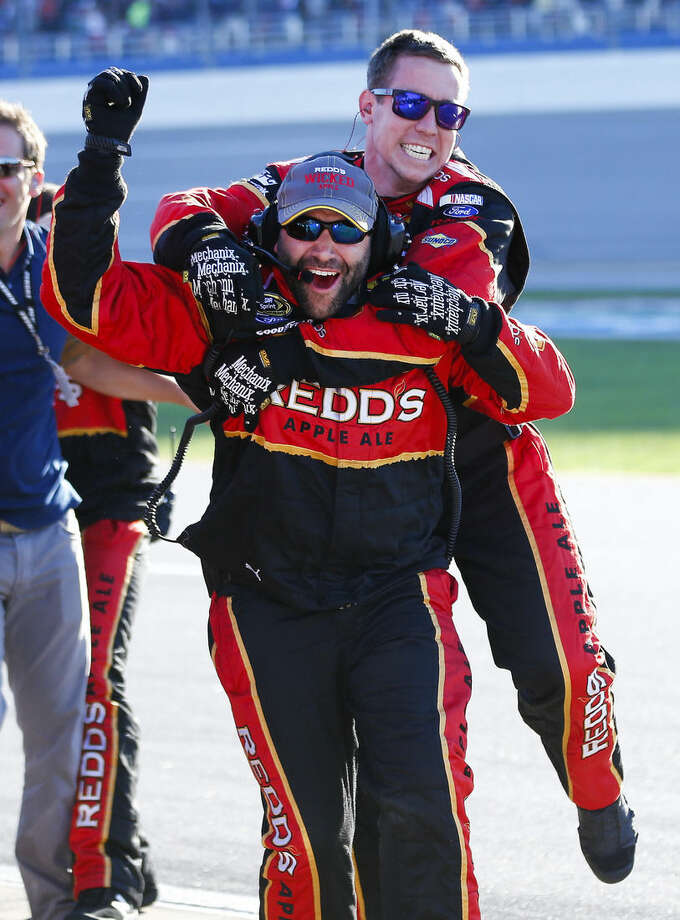 Members of Brad Keselowski's crew celebrate after he won the NASCAR Sprint Cup Series auto race at Talladega Superspeedway, Sunday, Oct. 19, 2014, in Talladega, Ala. (AP Photo/John Bazemore)