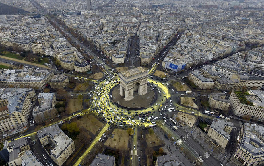 This photo provided by environmental group Greenpeace shows the Arc de Triomphe roundabout painted with yellow by activists, Friday, Dec.11, 2015. The protest is one of many activist actions linked to the COP21, the United Nations Climate Change Conference. (Greenpeace via AP)