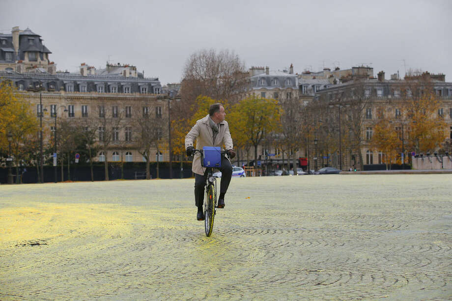 A man rides his bicycle on yellow paint poured on the street during a protest by activists from environmental group Greenpeace on the Champs-Elysee in Paris, Friday, Dec. 11, 2015 . The protest is one of many activist actions linked to the COP21, the United Nations Climate Change Conference. (AP Photo/Christophe Ena)