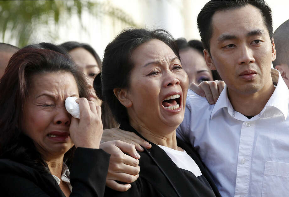 Trung Do Nguyen, right, comforts his mother, Van Thanh Nguyen, at a wake for his sister and her daughter, Tin Nguyen, at the Peek Funeral home in Westminster, Calif., on Friday, Dec. 11, 2015. Nguyen died in the mass shootings in San Bernardino, Calif., last Wednesday, Dec. 2. Woman at left is unidentified.(AP Photo/Nick Ut)