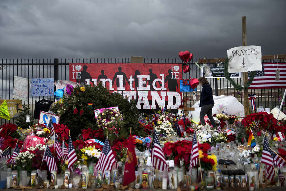 Erica Alvarez, right, pays her respects at a makeshift memorial near the Inland Regional Center, Friday, Dec. 11, 2015, in San Bernardino, Calif. 14 people were killed in last week's fatal shooting at the regional center. (AP Photo/Jae C. Hong)