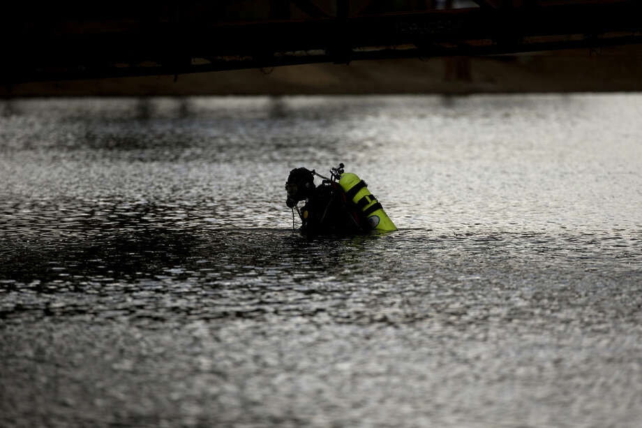 A member of the FBI dive team searches Seccombe Lake Friday, Dec. 11, 2015, in San Bernardino, Calif., for evidence in connection with last week's fatal shooting at Inland Regional Center, The FBI says divers are searching the lake because leads indicate the shooters who killed 14 people at a holiday party had been in the area. (AP Photo/Jae C. Hong)