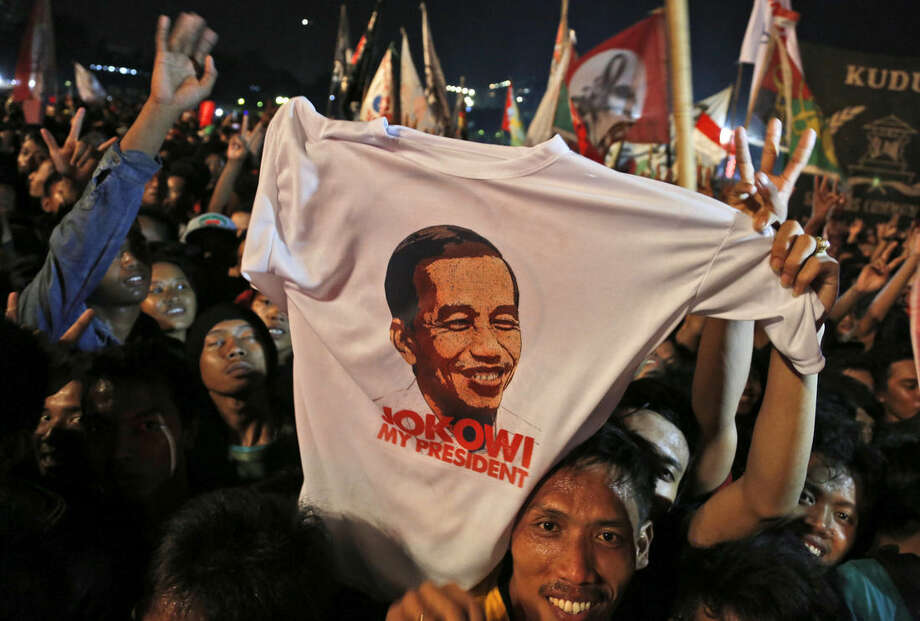 Supporters hold up a T-shirt showing an image of Indonesian President Joko Widodo during a celebration after his inauguration as the country's seventh president at the National Monument in Jakarta, Indonesia, Monday, Oct. 20, 2014. (AP Photo/Dita Alangkara)