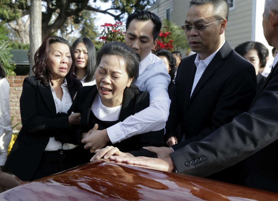 AP photo/Nick UtTrung Do embraces his mother Van Thanh Nguyen, center, mother of Tin Nguyen, as she weeps over her daughter's coffin during her wake at the Peek Funeral home in Westminster, Calif., Friday. Nguyen died in the mass shooting in San Bernardino, Calif., on Dec. 2.