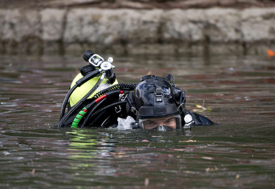 A member of the FBI dive team searches Seccombe Lake, Friday, Dec. 11, 2015, in San Bernardino, Calif., for evidence in connection with last week's fatal shooting at Inland Regional Center, The FBI says divers are searching the lake because leads indicate the shooters who killed 14 people at a holiday party had been in the area. (AP Photo/Jae C. Hong)
