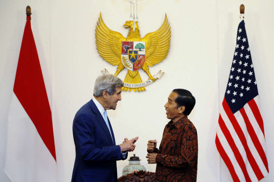 Indonesia's newly inaugurated President Joko Widodo, centre right, welcomes US Secretary of State John Kerry to the Presidential Palace, in Jakarta, Indonesia, Monday, Oct. 20, 2014. Widodo completed a journey from riverside shack to presidential palace on Monday, cheered through the streets following his inauguration by tens of thousands of ordinary Indonesians in a reminder to the opposition-controlled parliament of the strong grass-roots support that swept him to power. (AP Photo/Brian Snyder, Pool)