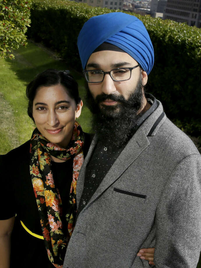 In this Dec. 11, 2015, photo, Darsh Singh, right, poses for a photo with his wife, Lakhpreet Kaur, outside his office in Dallas. It happens regularly: Someone sees a man with a turban and beard and hurls anti-Muslim slurs his way, or worse. Members of the Sikh religion, like Singh and his wife, also are feeling vulnerable as anti-Islamic sentiment heats up across the U.S., but instead of distancing themselves from Muslims, members of this southeast Asian religion are working with them to combat hateful rhetoric and dispel misconceptions about their respective faiths. (AP Photo/LM Otero)