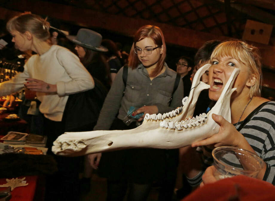 Nina Smith, right, tries out a Maine moose jaw, Sunday, Dec. 13, 2015, at the Morbid Anatomy Museum Holiday Flea Market in the Brooklyn borough of New York. As the holiday season gets into full swing, shoppers have been flocking to a Brooklyn flea market for gifts in a category all their own. About a dozen vendors displayed their horrific wares Sunday at the holiday market. People waited in long lines to get in. (AP Photo/Kathy Willens)