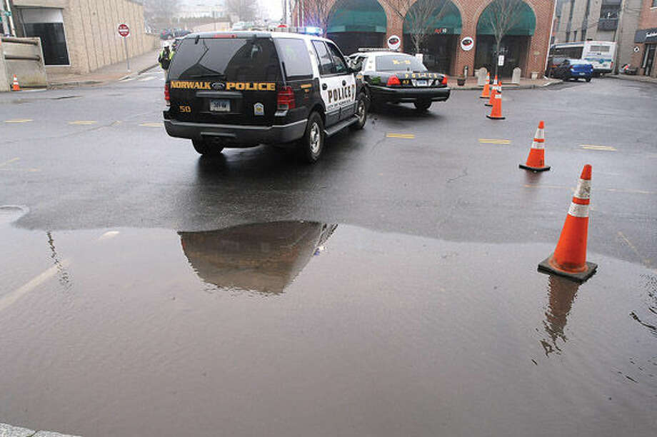 A water main break in the areas of Wall Steet, High Street and Main Street in Norwalk on Monday. At 11:00 am workers were trying to pinpoint the location of the break. Hour photo/Matthew Vinci