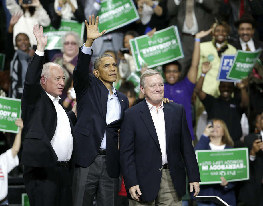 President Barack Obama, center, stands with Illinois Gov. Pat Quinn, left, and U.S. Sen. Dick Durbin, during an early voting and campaign rally for Illinois Gov. Pat Quinn at Chicago State University Sunday, Oct. 19, 2014, in Chicago. Early voting in Illinois starts Monday for the Nov. 4, election. (AP Photo/Charles Rex Arbogast)