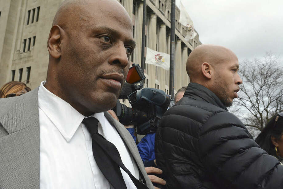 Chicago Police Cmdr. Glenn Evans, left,who was accused of shoving his gun down a suspect's throat and pressing a stun gun to the man's groin in 2013, leaves the Criminal Courts Building in Chicago on Monday, Dec. 14, 2015, after being acquitted on battery and misconduct charges. (Brian Jackson/Chicago Sun-Times via AP) CHICAGO TRIBUNE OUT, MANDATORY CREDIT, MAGS OUT, NO SALES