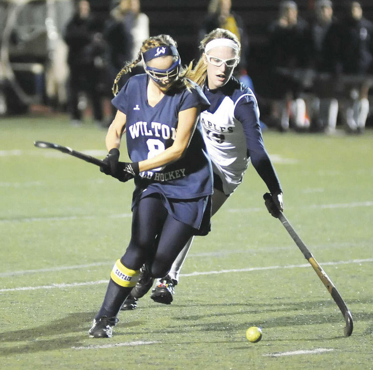 Hour photo/John Nash Wilton's Kristen Godin, front, pulls back her stick before driving the ball into the cage for a goal during her team's 6-0 win over Staples on Monday night in Westport. Behind Godin, Staples' Elizabeth Bennewitz tries to defend.