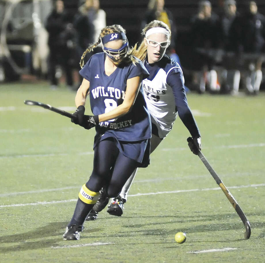 Hour photo/John NashWilton's Kristen Godin, front, pulls back her stick before driving the ball into the cage for a goal during her team's 6-0 win over Staples on Monday night in Westport. Behind Godin, Staples' Elizabeth Bennewitz tries to defend.