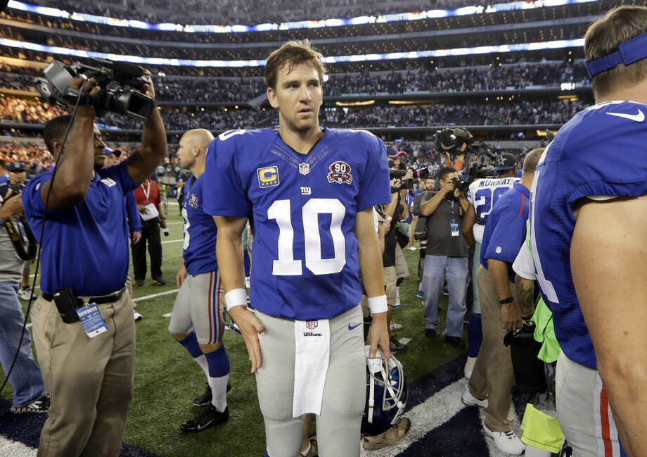 New York Giants quarterback Eli Manning (10) walks off the field following a 31-21 loss to the Dallas Cowboys in an NFL football game, Sunday, Oct. 19, 2014, in Arlington, Texas. (AP Photo/LM Otero)