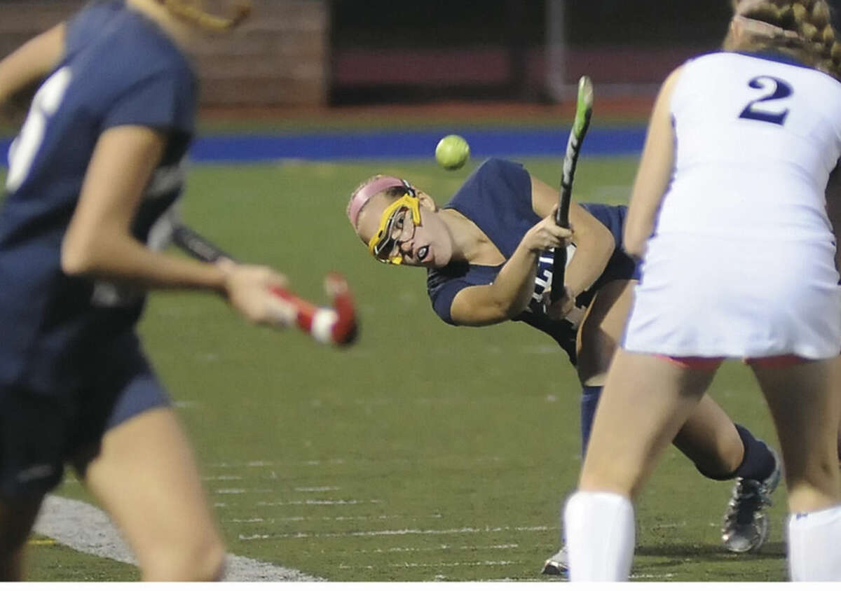 Hour photo/John Nash Wilton's Jillian Mahon, center, flicks the ball between a hole in players Bridget Ward, of Wilton, left, and Jamie Tanzer of Staples, right, during Monday's game in Westport. Wilton won, 6-0.