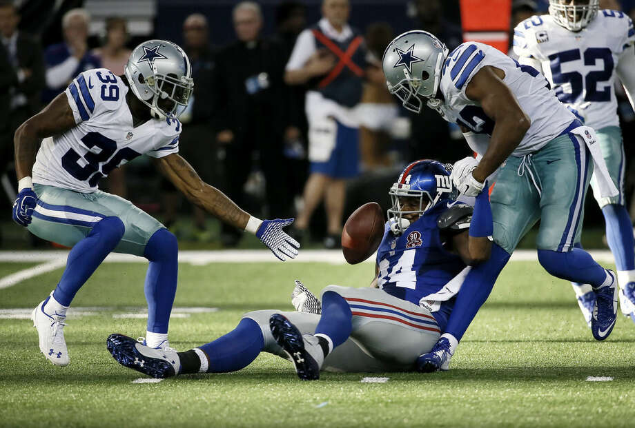 Dallas Cowboys cornerback Brandon Carr (39) watches as free safety Barry Church (42) causes New York Giants tight end Larry Donnell (84) to fumble during the second half of an NFL football game, Sunday, Oct. 19, 2014, in Arlington, Texas. cornerback Brandon Carr (39) reaches for the ball. (AP Photo/Brandon Wade)