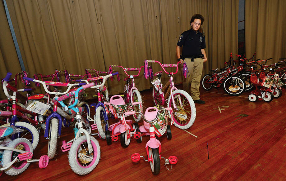 Hour photo / Erik Trautmann Norwalk Police Explorer Chris Rodrigues stands over the 30 bikes to be given out at The Norwalk Community Policing Division Children's Christmas Party Saturday at Columbus Magnet School.